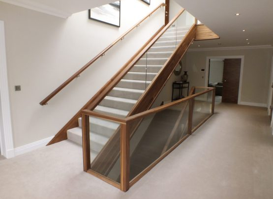 walnut staircase, cream carpet, glass balustrade