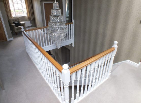 white staircase, oak handrail and bottom step, chandelier