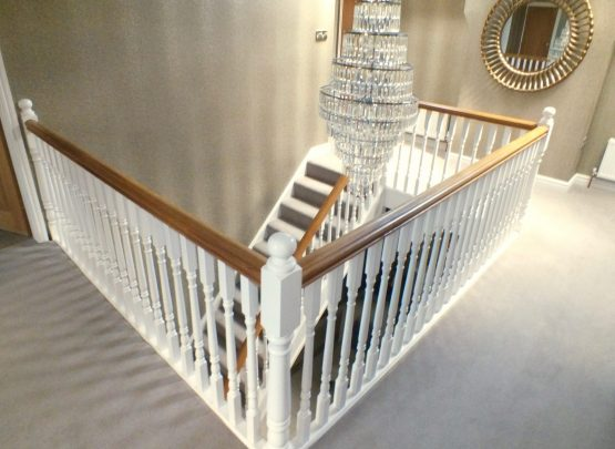 white and oak staircase with chandelier